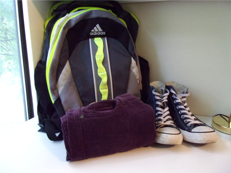 To keep my packing light, I limit my bag size and shoe options, and use space-saving hacks like rolling my pants up.