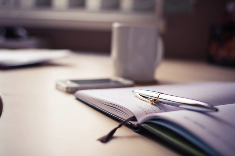 bullet journal on table with pen and coffee cup